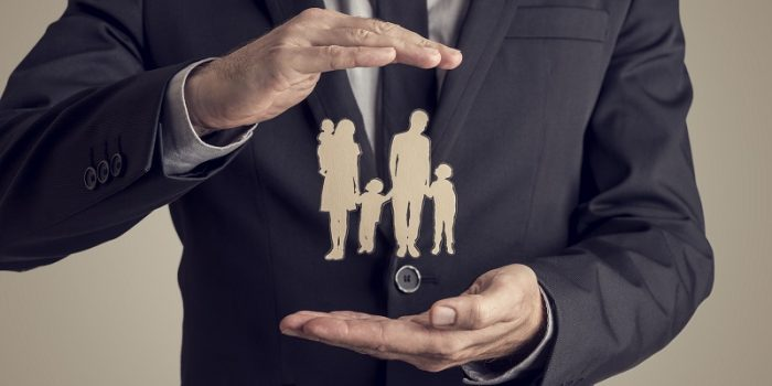 Retro Style Image Of A Businessman Protecting Family Silhouette